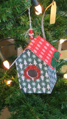 Leeg theedoosje beplakt met kerstpapier werd een vogelhuisje voor in de kerstboom.