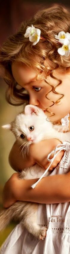 Adorable little girl with flowers in her hair holding a cute little pretty white kitten. Precious photograph.