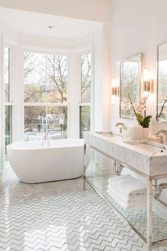 wow - bathroom in all white! Chevron tile pattern floor, free standing tub, huge windows, double vanity, marble, wall sconce lights. All white bathroom. home decor. interior decorating. bathroom inspo