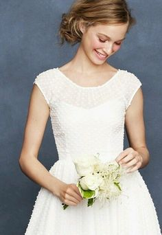 There is something so crisp, pure, and delicate about a vintage looking wedding dress. The Carenna by J. Crew has a Swiss dot sheer silk overlay with a sweetheart neckline peering through. Cap sleeves and a fitted bodice make this the perfect dress for an outdoor garden wedding, or for dancing the night away at your reception.