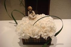 A sweet arrangement with an angel. White small floral arrangement, white carnations, floral design ideas.
