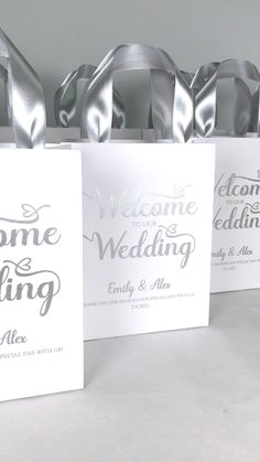 Elegant wedding welcome bags with silver satin ribbon handles and custom names. Chic personalized gift bags for wedding favors for guests. #welcomebags #weddingwelcomebags #giftbags #personalizedgifts #weddingfavor #weddingfavors #weddingbags #weddingfavorideas #weddingparty #favorbags #weddingwelcome #weddingparty #elegantwedding #silverwedding