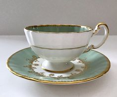 Vintage Aynsley china tea cup and saucer, made in England. White and green ground with gold gilding, and a single pink rose inside the bowl of the cup and saucer. It is in good condition, no chips, cracks or crazing. Please Note: The items I sell are not new, they are vintage or