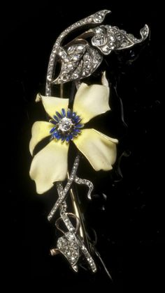 An Art Nouveau clematis spray brooch, France, ca.1890. Composed of gold, silver and matted enamel, the leaves fully set with rose-cut diamonds and the flowerhead decorated with a soft yellow enamel. The centre highlights with blue enamel and a diamond. A Clematis is a symbol for mental beauty.