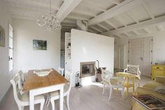 Casale a Ostra Vetere, vista della zona soggiorno con grande camino centrale, soffitto con travi a vista tinteggiate di bianco, Progetto Arch.Luca Braguglia