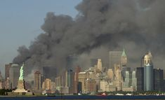 On September 11, 2001, thick smoke billows into the sky from the area behind the Statue of Liberty, lower left, where the World Trade Center towers, now collapsed, had stood. (AP Photo/Daniel Hulshizer)