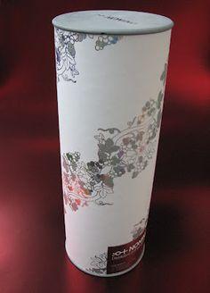 Particole ed elegante cilindro per una bottiglia di Grappa Nonino, si contraddistingue per tappi grigi in legno tornito, carta di rivestimento stampata con laser, lamina e glitter.