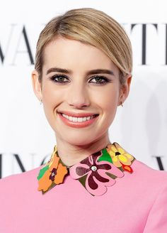 Emma Roberts' deep side parted hair pulled back, peach lips, and plum-colored eyeliner on her bottom lash line.