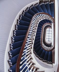 "ric-rac"" detailing on the navy stair-runner curling around this spiral staircase by Anthony Baratta"