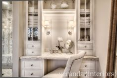 Beautiful built-in white dressing table nook with nickel pulls, gray and white marble countertop and above counter, glass front cabinets with shelf over a frameless mirror illuminated by Thomas O'Bryant Sconces paired with Restoration Hardware Martine Chair.