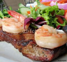 Barbequed steak topped with shrimp and served with salad.