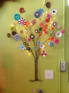 Display of vintage flower brooches on a metalwork tree, with tiny lights added.  At Passion Window Gallery in Terre Haute, Indiana