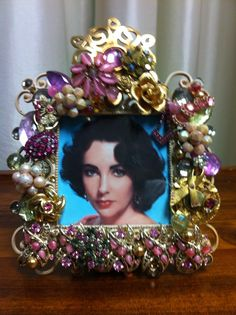 """Ever hear that """"Liz"""" had breast cancer?  Well, here she is all wrapped in The Color for the Cure - pink - vintage costume brooches, pins, earrings and more!  Check out the Breast Cancer Awareness pin just to the right of her.  Not one more pink anything can fit!  Quality everything on sturdy frame with velvet back. $225 www.thequeensdesigns.com."""
