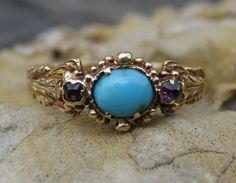 Victorian Turquoise & Garnet Ring 18k with turquoise cabochn and two garnet accents.