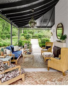 In a Nashville house designed by Markham Roberts, a ceiling painted in Benjamin Moore Aura in Black Knight makes for a handsome porch that's used year-round thanks to a fireplace and fans. The teak sofa and armchairs by Restoration hardware are covered in kravet Navy canvas and Quadrille's Island ikat custom-printed on Sunbrella fabric. Palecek wingback chairs. Paul Ferrante pendant.