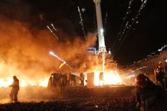 A firework explodes amid flames during clashes between anti-government protesters and riot police at Kiev's Independence Square