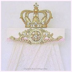 This amazing, 20 wooden teester has been painted in French Ivory and embellished with pretty, pink, organza and satin ruffle trim and crystal clear beaded fringe. It has a stunning, golden, Fleur de Lis motif applique (with a vintage look to it) on the front and a matching Metallic Gold Fleur de Lis crown on top. This spectacular bed crown teester has been bedecked in splendor with dazzling crystal rhinestones to complete this glamorous look! Customers have used these over Princess cribs…