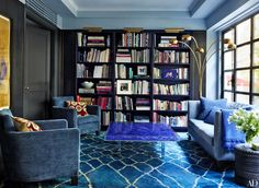 In the library, the pair of Christian Liaigre armchairs and the custom-made sofa and its pillows are all covered in Manuel Canovas fabrics; the cocktail table is by Yves Klein, while the Moroccan carpet from Woven Accents and the floor lamp in the corner are both vintage. Brass picture lights by Ralph Lauren Home top the bookshelves.