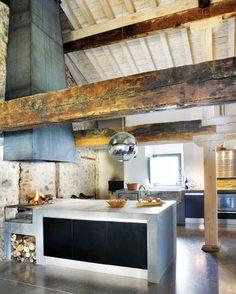 ¿Esta cocina te parece rústica o moderna? La lámpara y la encimera de cemento le dan el toque moderno y las vigas de madera envejecida, el toque rústico. El nuevo estilo rústico moderno es tendencia.