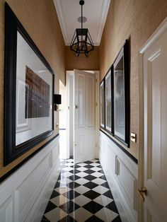 Black-and-white checkerboard flooring sets an elegant tone in the hallway. Lynn lined the walls with Pearl River Jute from Thibaut's Grasscloth collection. Vaughan's Lion Head wall lights add a hint of glamour, while a black metal pendant introduces a graphic note.