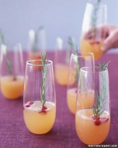 Sparkling pear and cranberry cocktail with dried cranberries and rosemary