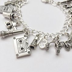 ►  This beautiful charm bracelet is inspired by Jay Ashers novel and hit Netflix show, Thirteen Reasons Why. There are a mix of 17 antique silver and silver plated charms that symbolize each character and the story that unravels around them, which are then attached onto a 7 inch silver plated chain.   The perfect gift for any 13 Reasons Why fan!  Charm Attachments: Bottle Basketball Vest To Do List Cheerleader Hot Chocolate Hair Dryer and Scissors School Bus Bike Headphones Number 13 Nail…