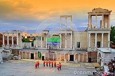 Bulgarian folklore group dancing at ancient Roman Amphitheater  stage during the 3rd Balkan folklore festival and beautiful scenic view of  Plovdiv city at sunset,Bulgaria.