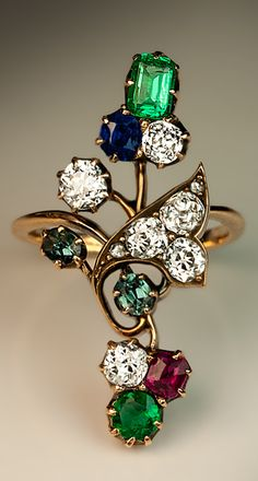 An Antique Art Nouveau Gemstone Flower Ring Russian, made in Kazan between 1908 and 1917 The 14K gold ring is designed as a stylized flower set with six bright white and sparkling old cushion cut diamonds (approximately 1.32 ct total weight), two rose cut diamonds, two emeralds (0.41 ct tw), two alexandrites (0.21 ct tw), one ruby (0.16 ct) and one sapphire (0.20 ct). The ring is marked with 56 zolotnik gold standard and maker's initials