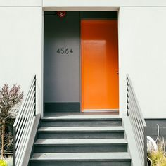Orange promotes optimism and warmth. What more could you ask for in a front door? The jolt of color balances the chic concrete grays. Bright Front Doors, Orange Front Doors, Beautiful Front Doors, Orange Door, Yellow Doors, Orange House, Front Door Colors, Mid Century Modern Door, Door Design