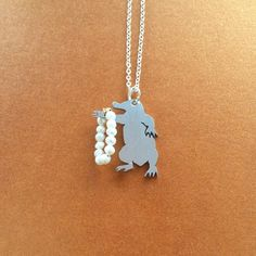 """DESCRIPTION  Niffler Silhouette Necklace Fantastic Beasts Inspired Handmade SHIPS FROM USA  You will receive one handcut Niffler necklace, made to look like Newt Scamander's niffler when discovered in the jewelry store. Chain measures 18"""" but can be made in any length you'd prefer. Pure grade aluminun, sterling silver, and freshwater pearl.  These are truly hand made pendants. While there will be minor differences from piece to piece, quality is my #1 priority. For the first time ever, these…"""