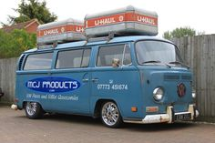 VW bay window bus with U-Haul carriers on roof