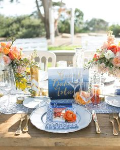 Goldvessels and votives holding bright and soft orange-hued arrangements from Twigg Botanicalswere the focal point on the long wooden reception tables. Theyalso featured bluepainted signs made by Peanut Press, and each table was named for a different island in the Bahamas.