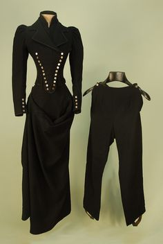 LADY'S BLACK WOOL 3-PIECE SIDESADDLE HABIT, c. 1885. Double breasted boned jacket with notched lapel over high neck insert, eleven mother of pearl buttons on each side. Fall front leggings with single button each side, leather stirrups, braided trim.