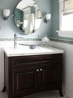 For a contemporary look with weightless appeal, pair a furniture-style vanity with a clear-glass vessel sink. The glass vessel prevents this small countertop from feeling cluttered. A sleek chrome faucet and sconces blend well with the clear glass. /