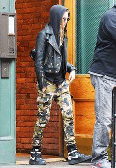 Cara Delevinge wears camo print cargo pants, Nike high tops, a black hoodie and a leather moto jacket.