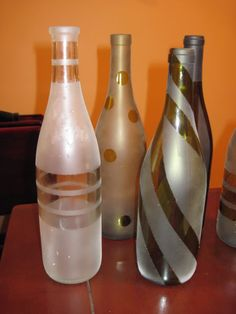 Take the label off of wine bottles, put painters tape in different designs, spray with spray paint, let dry, and peel off the tape. This would be a good idea for a centerpiece idea! A few at each table with different designs