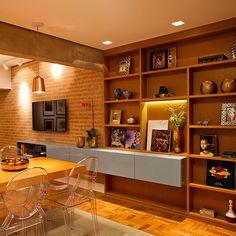 Sala linda, parede de tijolinhos atrás da tv, módulo na horizontal em azul na estante dá um contraste na paleta de cores. Projeto Scatena Arquitetura
