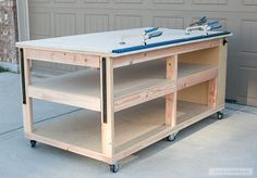 woodworking shop DIY Workbench with storage shelves - Learn how to build a DIY Mobile Workbench with Shelves and storage for quarts of paint and stain. Add a clamp track and magnetic strips to hold stray bits.