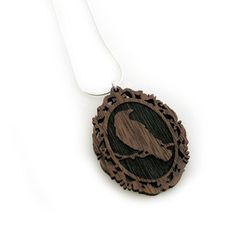 Crow Cameo Pendant Necklace  by Meagan Schafer - Inspired by the local crow population that flocks over Vancouver, the Crow Cameo Pendant Necklace is handcrafted from American black walnut. Spruce's eerie, beautiful design features a solitary crow resting on a leafless branch.
