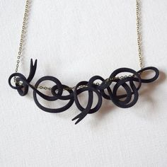 classy 3D printed intertwining black ribbon design that makes a uniquely different pendant. MONOCIRCUS
