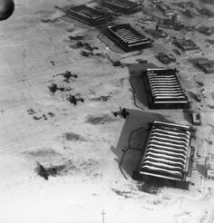Oblique aerial view of part of RAF Driffield, Yorkshire, in the winter snow, showing the five Type C hangars fronting the bombing circle and other buildings on the technical site. Armstrong Whitley Mark Vs of No. 77 Squadron RAF are parked on the airfield in front of the hangars.