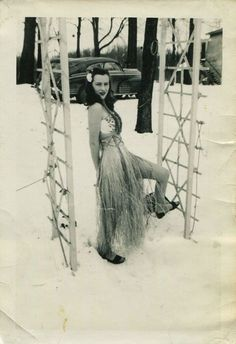 Hula skirt lady outside in the snow, 1940s.