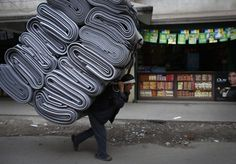 A Nepalese porter carrying a pile of mats walks along the streets of Kathmandu February 21, 2013. Most porters earn less than 3 dollars for carrying their load over 1 km (0.6 miles) each time. REUTERS/Navesh Chitrakar (NEPAL - Tags: SOCIETY)