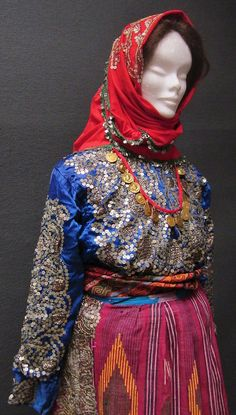 Close-up of a traditional bridal costume from the Sandıklı district (Afyon province).  Style of 1950-1975. The red head scarf, the shirt and the apron are adorned with metal sequins and 'tel kırma' embroidery (motives obtained by sticking narrow metallic strips through the fabric and folding them).  (Kavak Costume Collection-Antwerpen/Belgium).