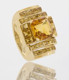 Boivin Citrine and Gold Art Deco Ring  A superb French Retro 18 karat gold ring with citrines by René Boivin. The Art Deco designed ring centers around a square cut intense color citrine that weighs approximately 3.85 carats with 6 rectangular calibre cut citrines framing the center stone that have the approximate total weight of 1.80 carats. In addition 28 square cut citrines that are channel set that step down and form the shank. They have the approximate total weight of 2.80 carats. C…