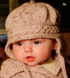 Free Knitting Pattern for Cable Panache Baby Hat - Cute earflap hat with cable band. 6-9 months though some Ravelrers have adapted for other sizes. Designed by Cindy Tuscany