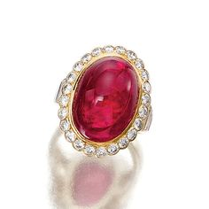 RUBY AND DIAMOND RING, VAN CLEEF & ARPELS.  The oval cabochon ruby weighing 16.50 carats bordered by brilliant-cut diamonds, the shoulders set with baguette stones, mounted in yellow gold, size 49,  signed Van Cleef & Arpels and numbered, French assay and maker's marks.