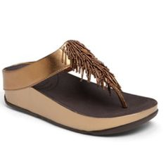"""Bronze FitFlop Cha Cha Sandals Relax in style with a comfy flip-flop featuring a low wedge. MICROWOBBLEBOARD™ midsole technology fuses three diagonal sections of triple-density EVA into a single, seamless, underfoot platform to absorb shock and diffuse high-pressure spots. 1 1/2"""" heel; 1"""" platform (size 9). Leather and rubber upper/rubber lining and sole. Fitflop Shoes"""