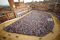 PIAZZA DEL CAMPO, DURING THE RUNNNG OF IL PALIO, THE FAMOUS HORSE RACE IN SIENA, ITALY.