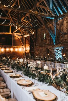 Rustic Barn Reception with Wood Slices, Antlers, Fairy Lights & Greenery - Kelsie Low Photography | Phil Collins Bridal Gown | Outdoor Ceremony & Rustic Barn Reception at Helmingham Hall Gardens in Suffolk | Floral Monsoon Flower Girl Dresses